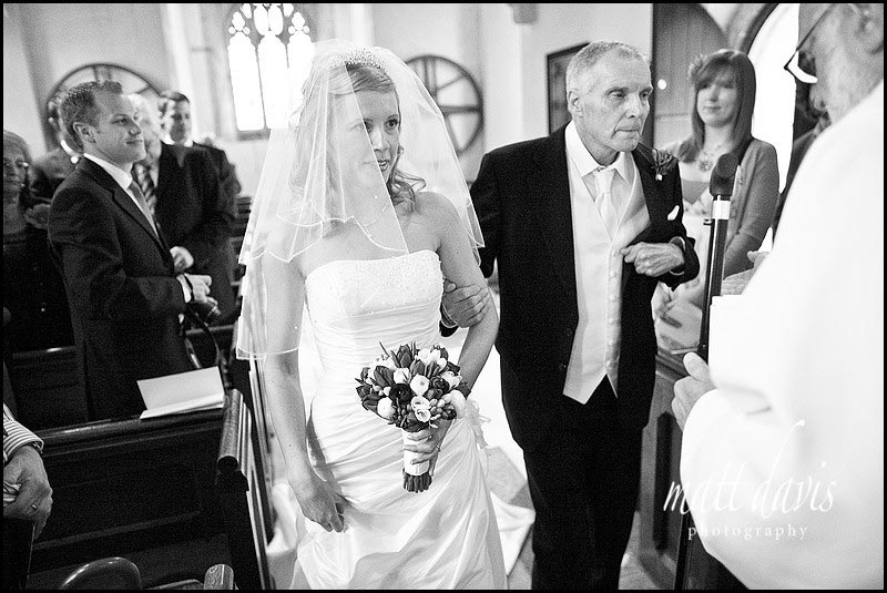 Bride walking down aisle at Barnsley Church in the Cotswolds