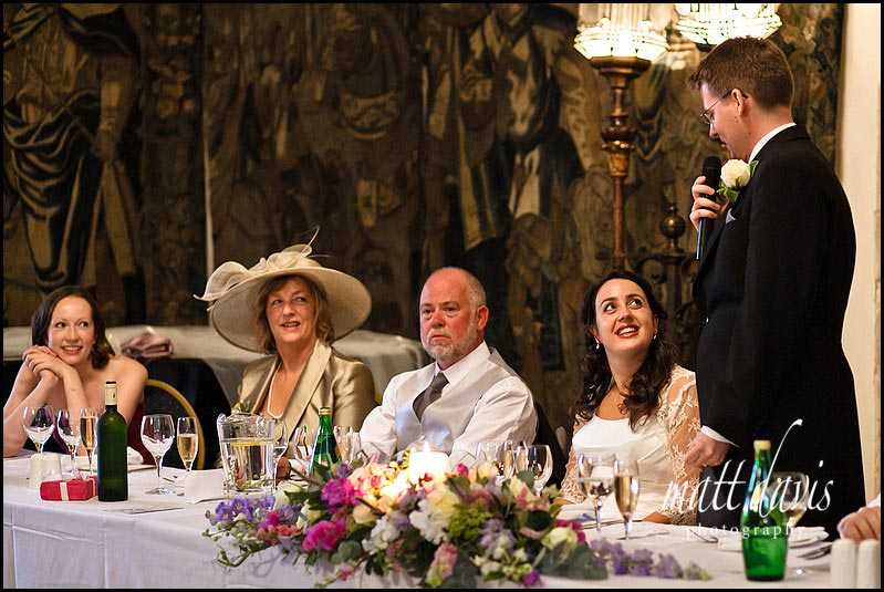 Bride smiles at groom during wedding speeches at Berkeley Castle