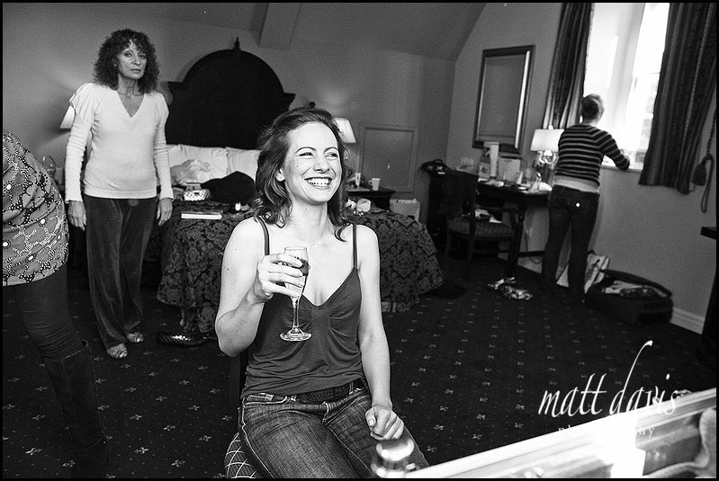 Bride drinking champagne whilst getting ready