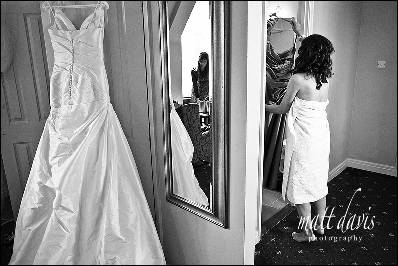 Bride in towel with wedding dress hung up
