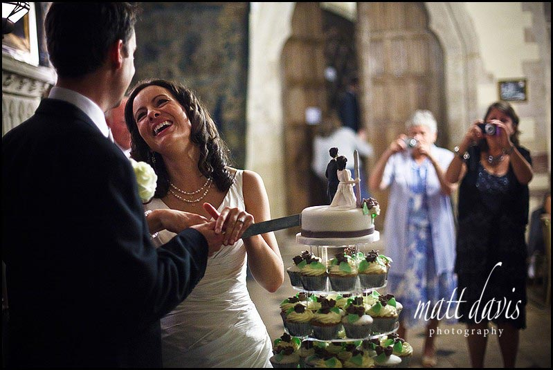 Bride and groom cutting wedding cake at Berkeley Castle
