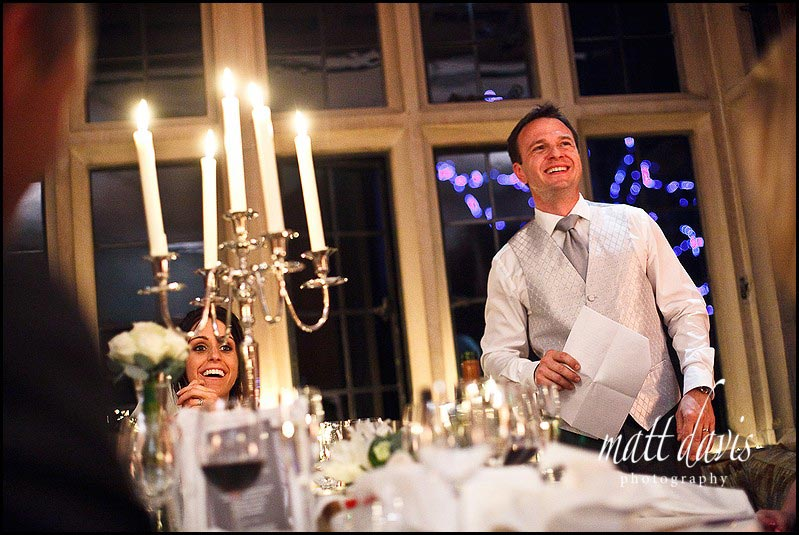 groom smiles during speeches at Speeches at Bibury Court