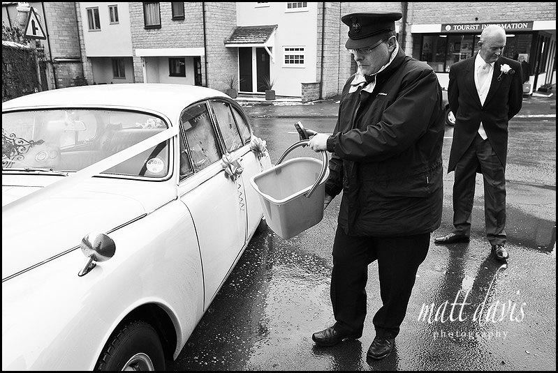 chauffeur cleaning vintage wedding car