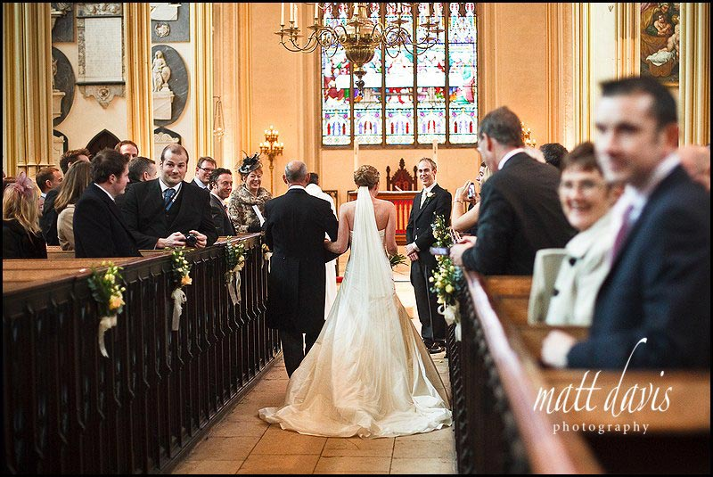 Bride walking down aisle at St Mary the Virgin Tetbury Church
