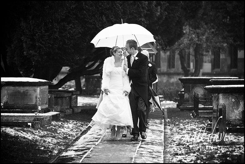 Bride with umbrella over head at winter wedding