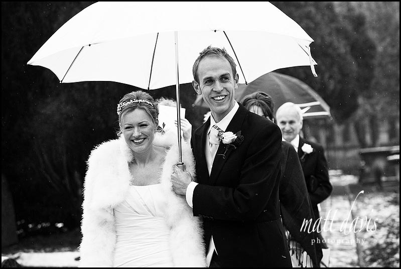 Bride with umbrella over head at wedding