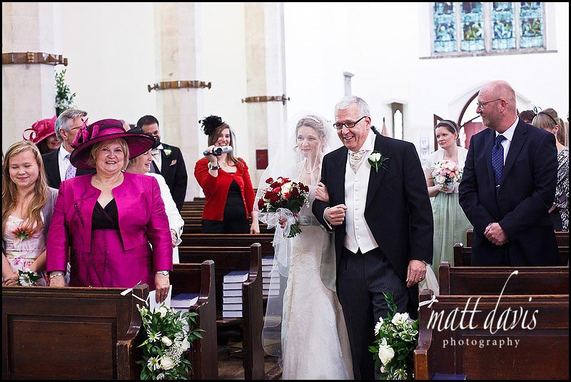 Bride walking down aisle at Holy Trinity Church in Minchinhampton
