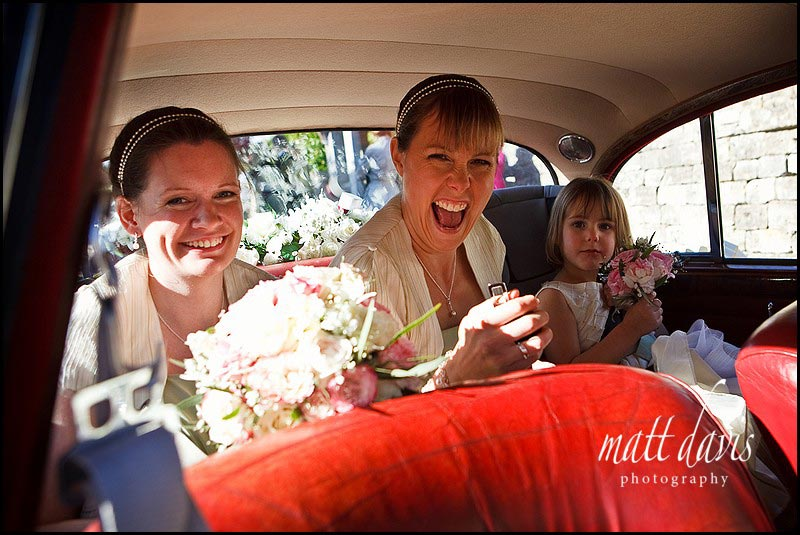 Bridesmaids in vintage wedding car