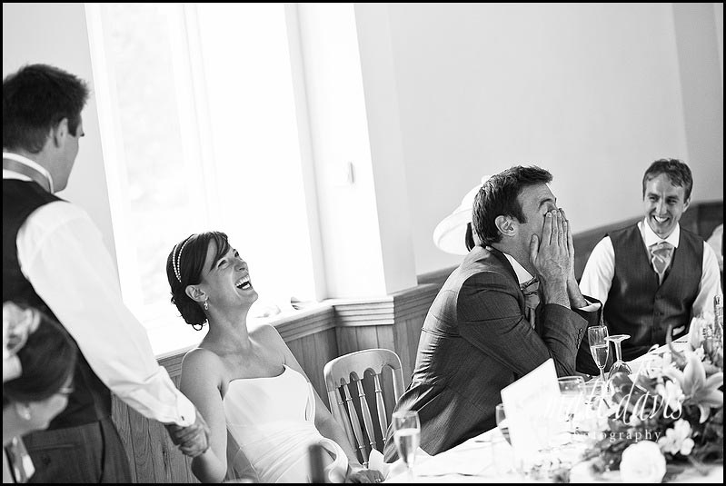 Laughing bride during wedding speeches at Delbury Hall