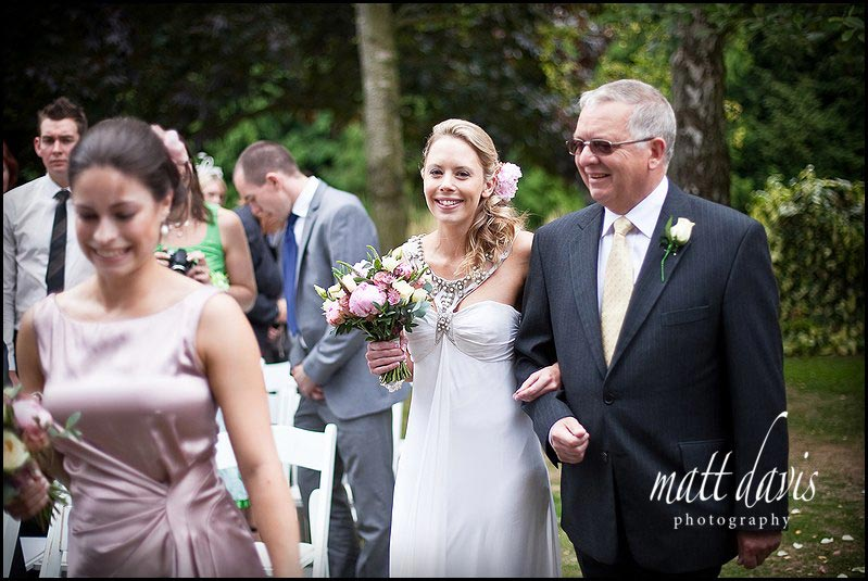 Brides arrival down the aisle at outdoor wedding ceremony