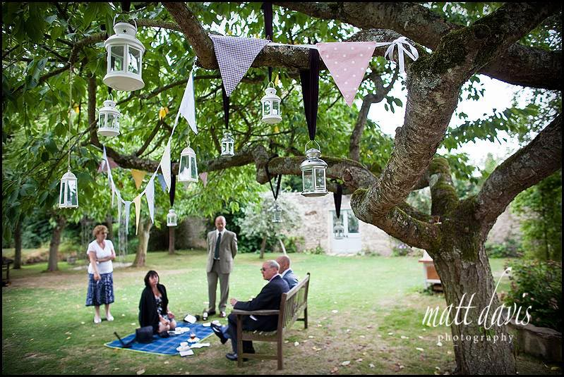 Pastel patterned bunting hung in trees at a wedding