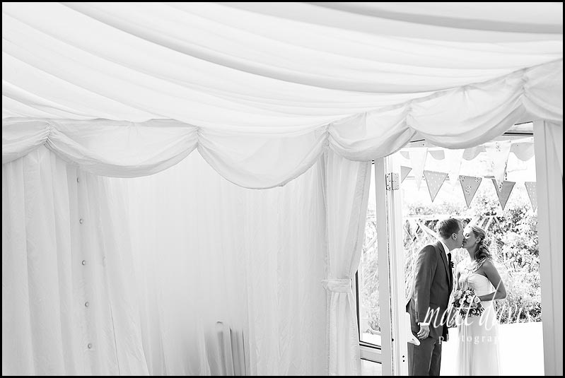 Bride and groom kissing outside marquee