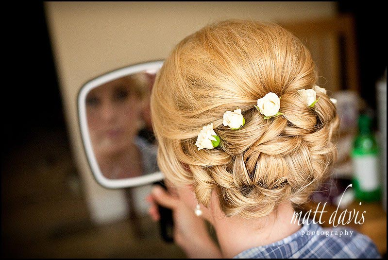 Wedding hair tied up in small ringlets with delicate flowers