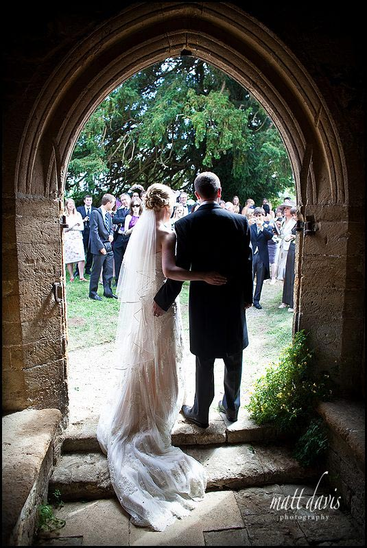 wedding photo at St Mary's Church, Swerford in the doorway