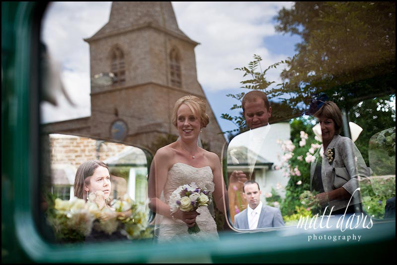 wedding photo of St Mary's Church, Swerford reflected in car window