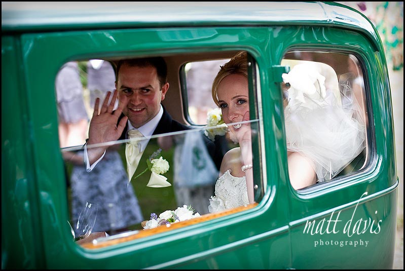 wedding couple in vintage wedding car leaving St Mary's Church, Oxfordshire