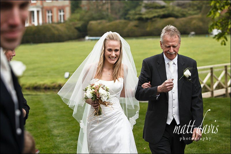 Bride and father walking up aisle of outdoor wedding ceremony