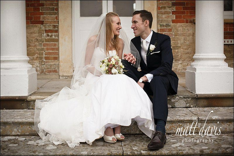 Bride and groom sat on steps at Ardington House