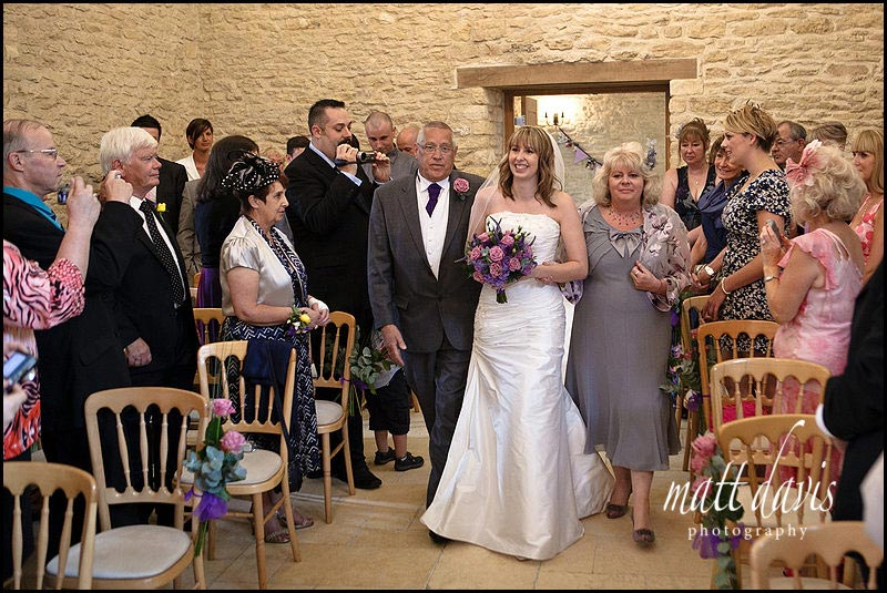 walking down the aisle at Kingscote Barn wedding
