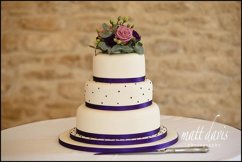 wedding cake with purple ribbon trim