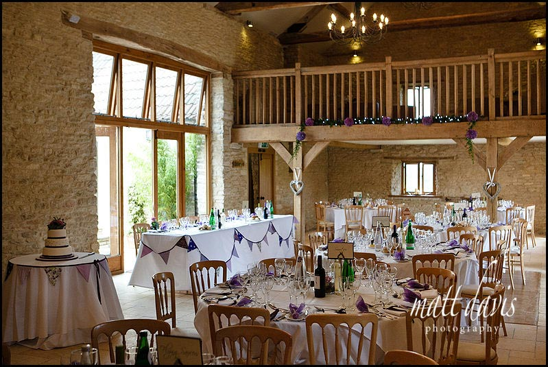Inside Kingscote Barn set for wedding breakfast.