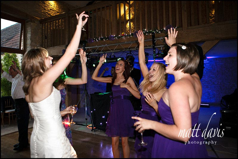 Bride and bridesmaids dancing at Kingscote Barn wedding