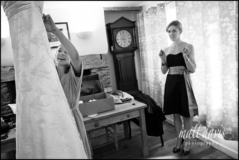 bride looking at wedding dress with excited bridesmaid