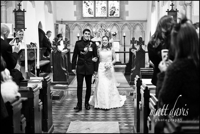 bride and groom leaving Kington St Michael Church after wedding