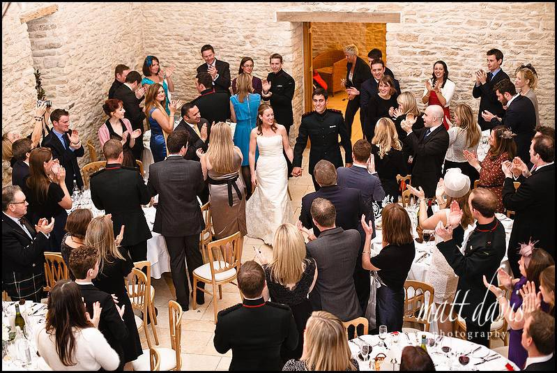 Guests inside Kingscote Barn clapping as bride and groom enter for dinner
