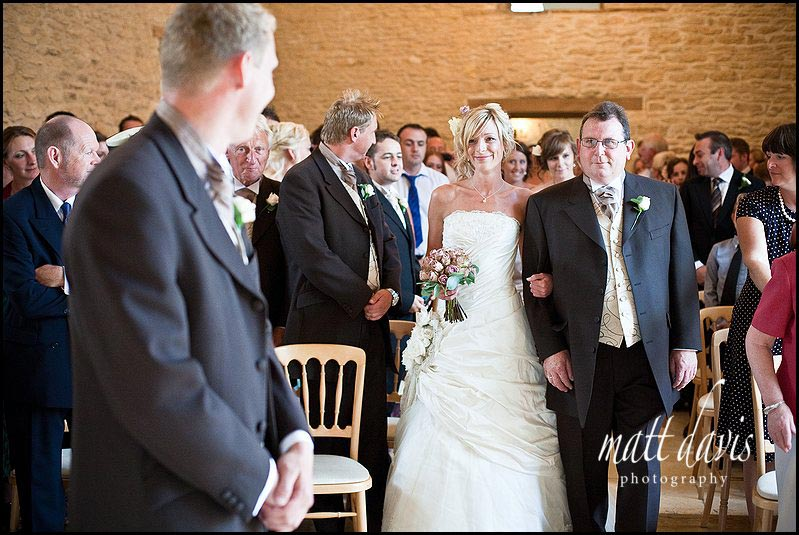bride at Kingscote Barn wedding walking down aisle