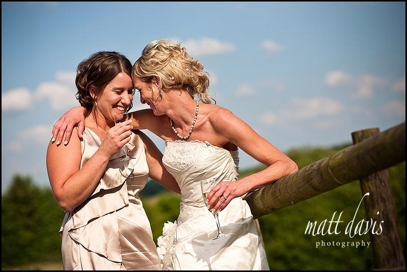 bride and bridesmaid laughing at Kingscote Barn wedding