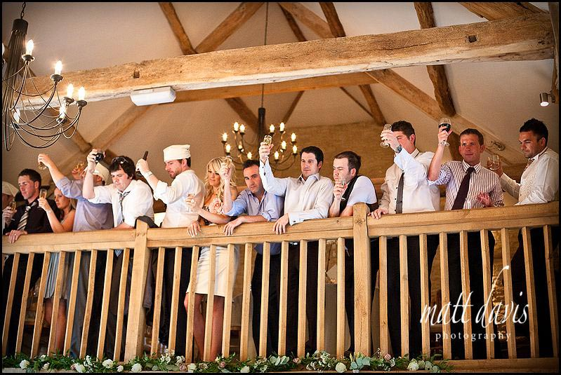 Wedding guests eating on the balcony area at Kingscote Barn