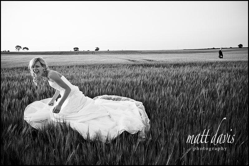 black and white photo of bride and groom in a field of corn at Kingscote barn