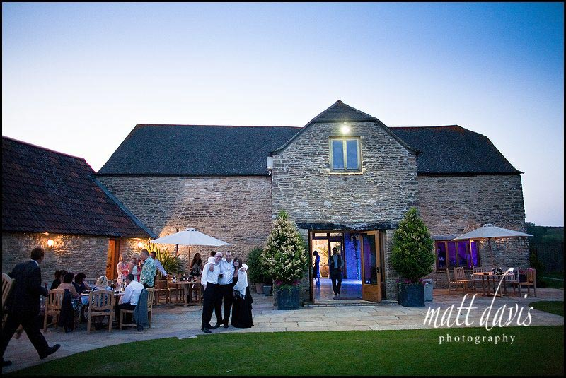 Kingscote Barn wedding venue with guests outside at night