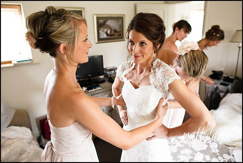 Bride and bridesmaids doing up wedding dress