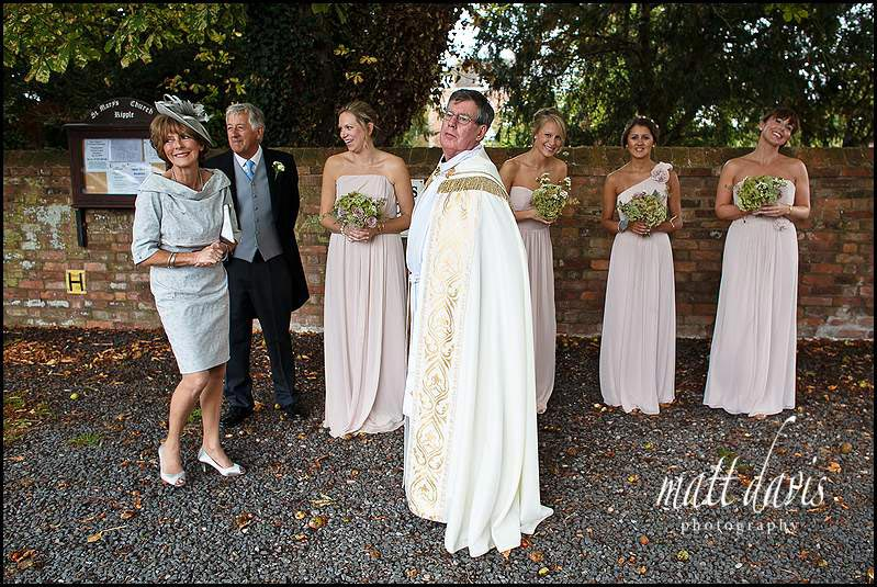 Bridesmaids waiting outside Ripple village church, Gloucestershire