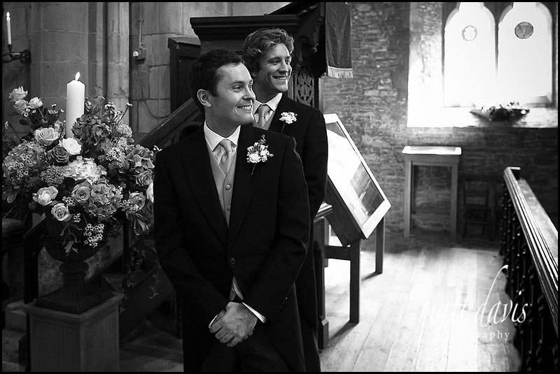 Groom watching bride walk down the aisle.