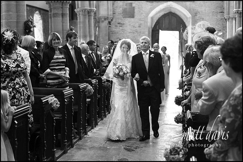 Bride walking down the aisle inside Ripple church, Gloucestershire