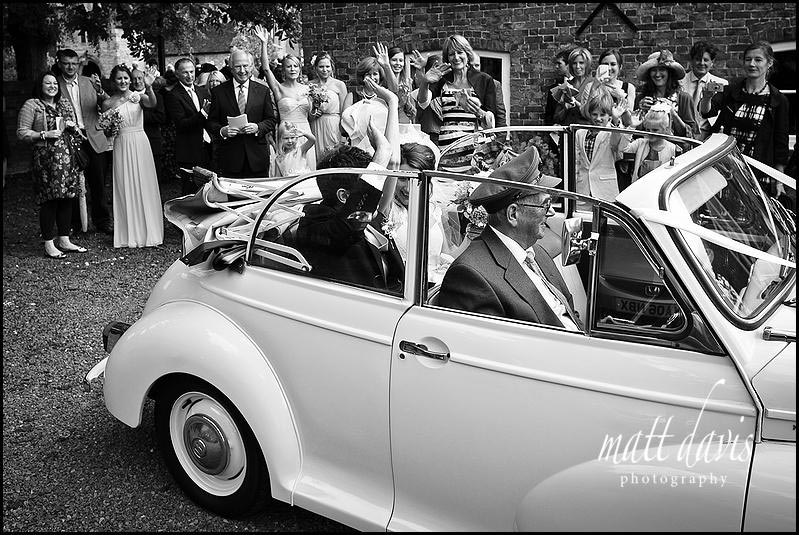 Wedding couple waving from vintage wedding car