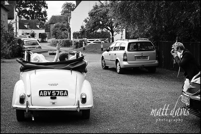 Wedding couple waving as they leave in vintage wedding car