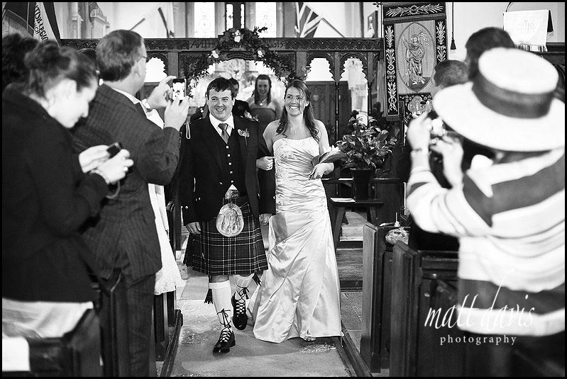 Bride and groom exiting Kingscote Church, Gloucestershire