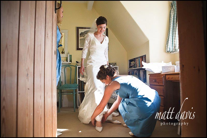 Brides shoes being put on by bridesmaids