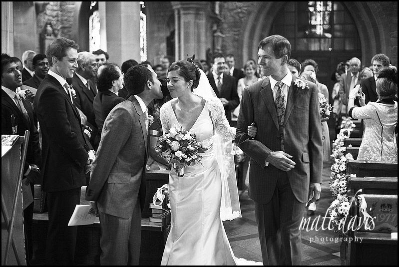 Bride kissing groom at bride arriving at St Mary's Church, Prestbury