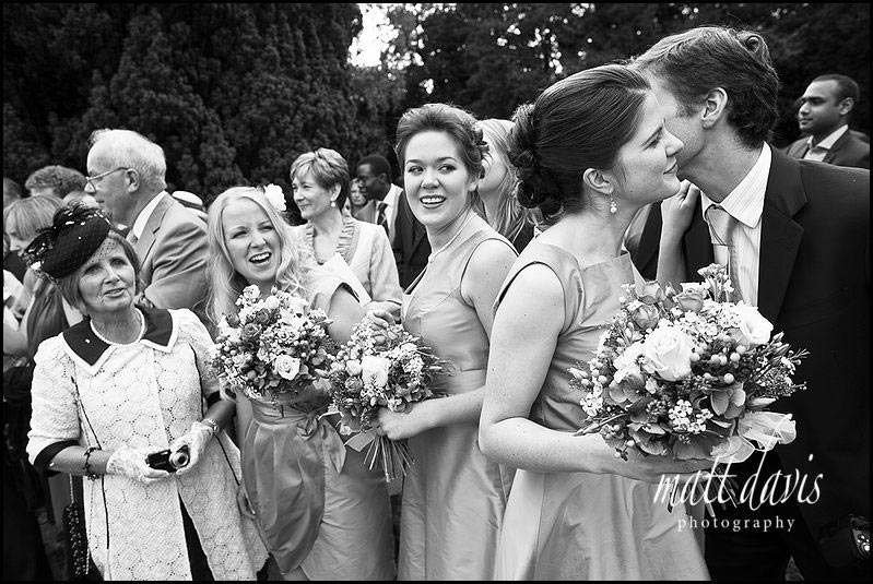 Bridesmaids kissing their partner at wedding