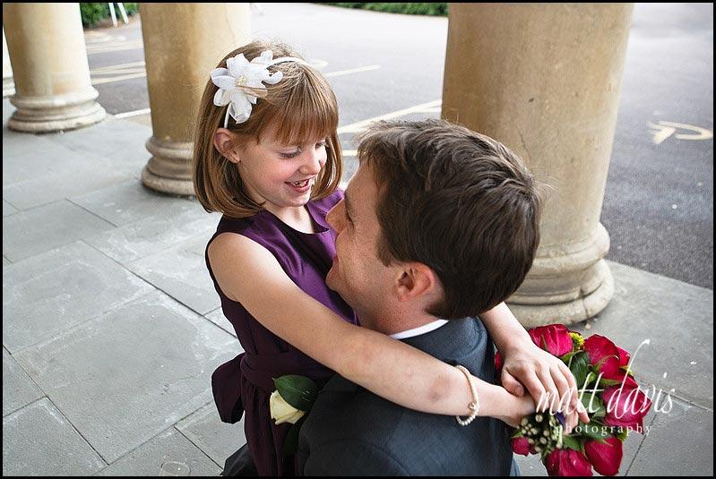 Small bridesmaid hugging groom