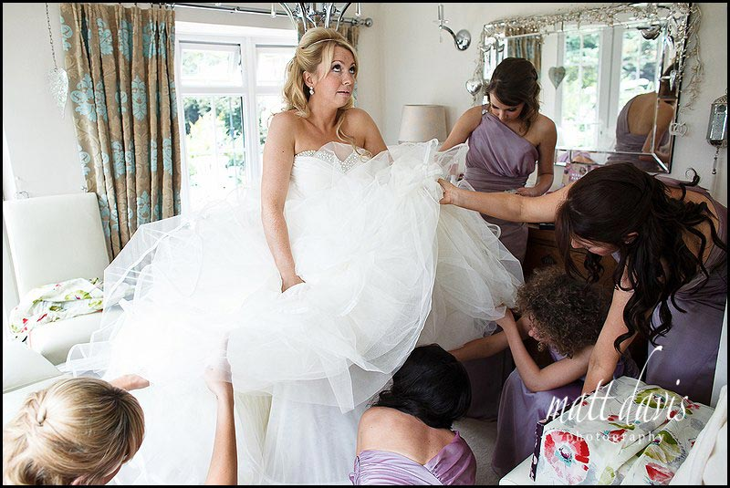 Wedding Photography of bride getting wedding dress on