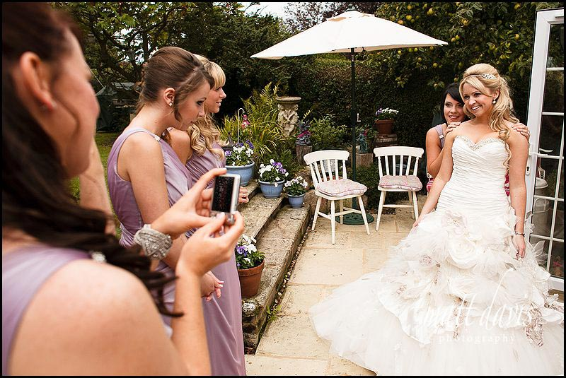 Bridesmaids photographing bride before wedding