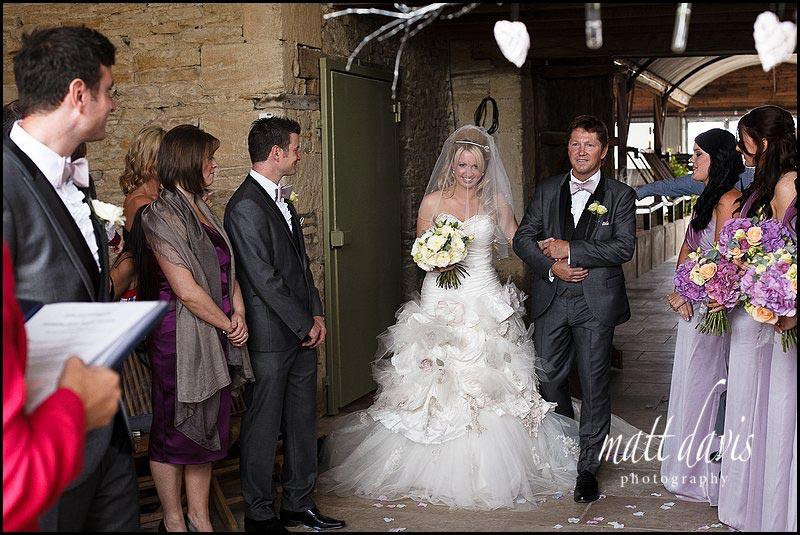 bride walking down aisle at Cripps Stone Barn