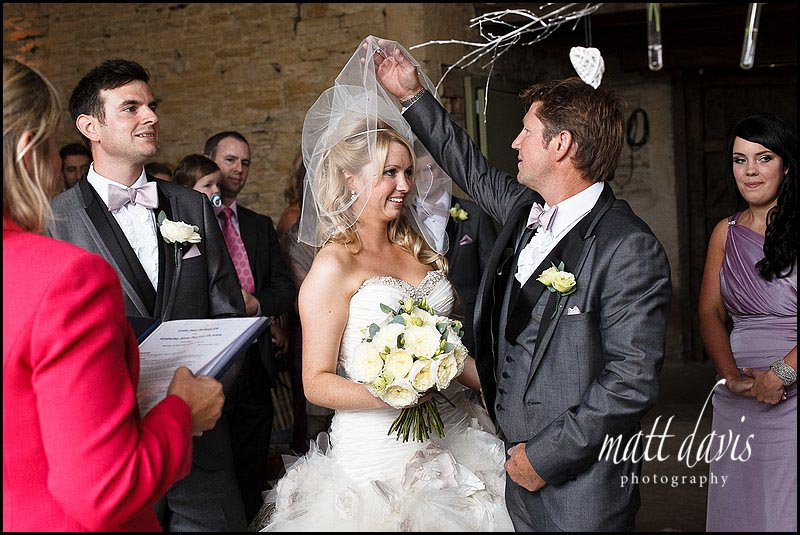 Bride having veil lifted of face at Stone Barn