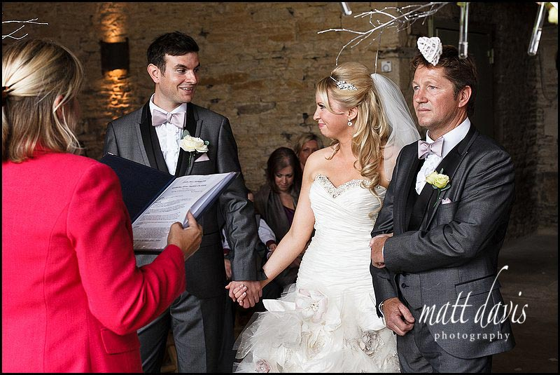Bride and groom during wedding ceremony at stone barn